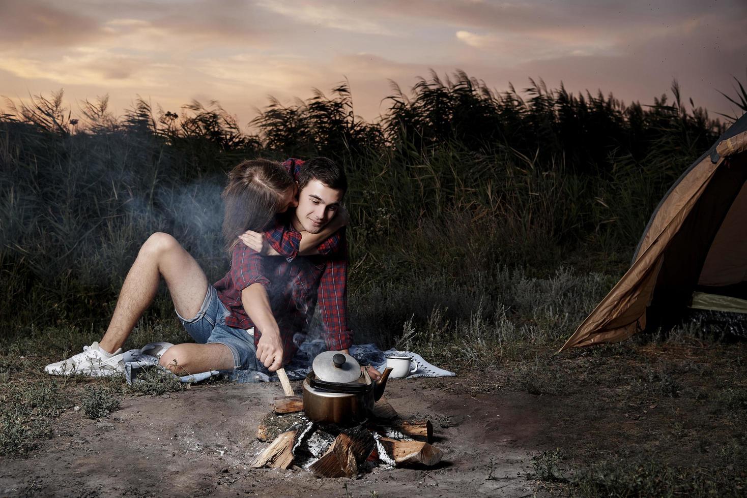 ungt par kramar vid elden foto