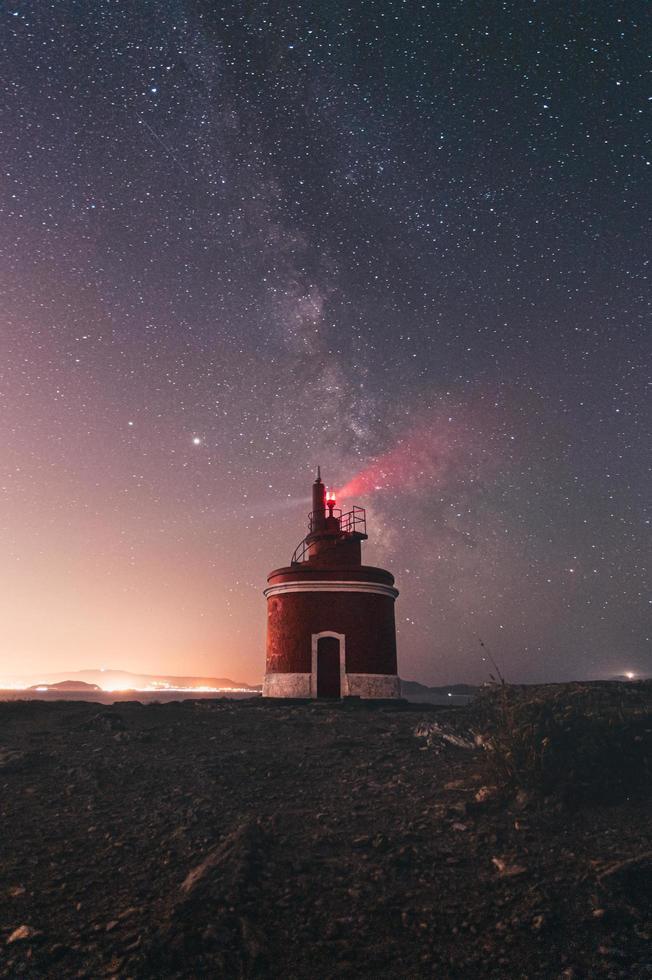fyr under stjärnklar natthimmel foto