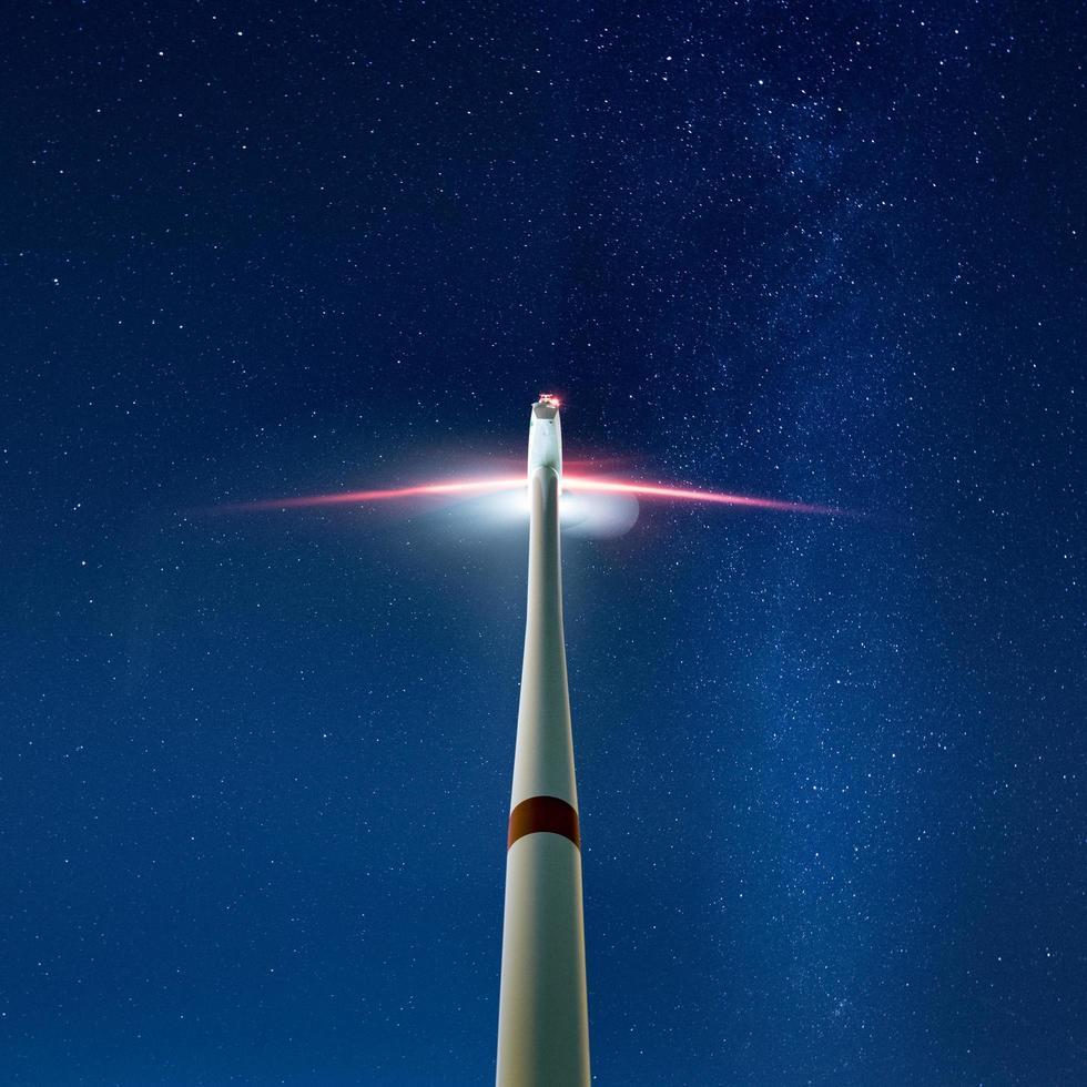 en upplyst vindkraftverk foto