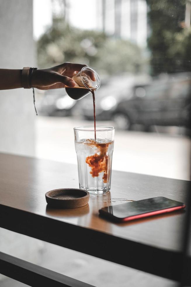 person som häller te i klart glas foto