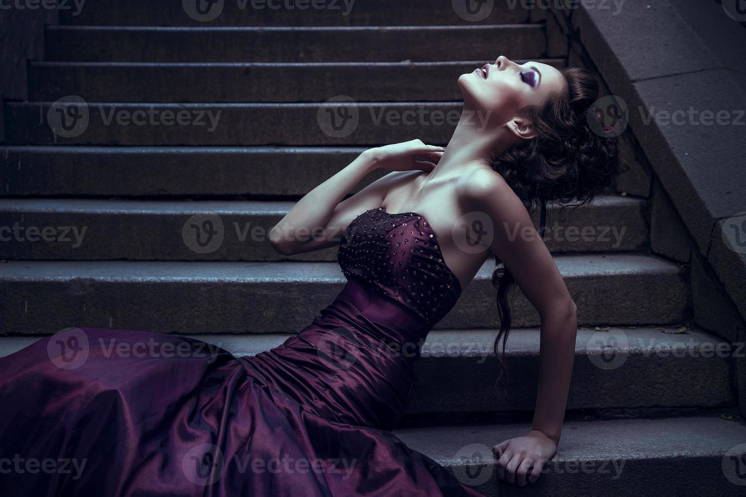 vacker kvinna i en violett klänning för fotografering foto