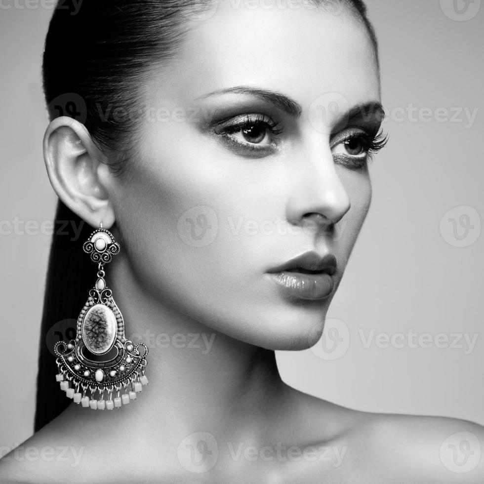 porträtt av vacker ung kvinna med örhängen. smycken och acce foto