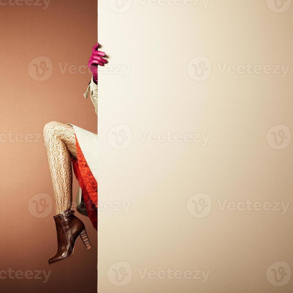 en kvinna som vandrar upp sin kjol som är halvtäckt av en vägg foto