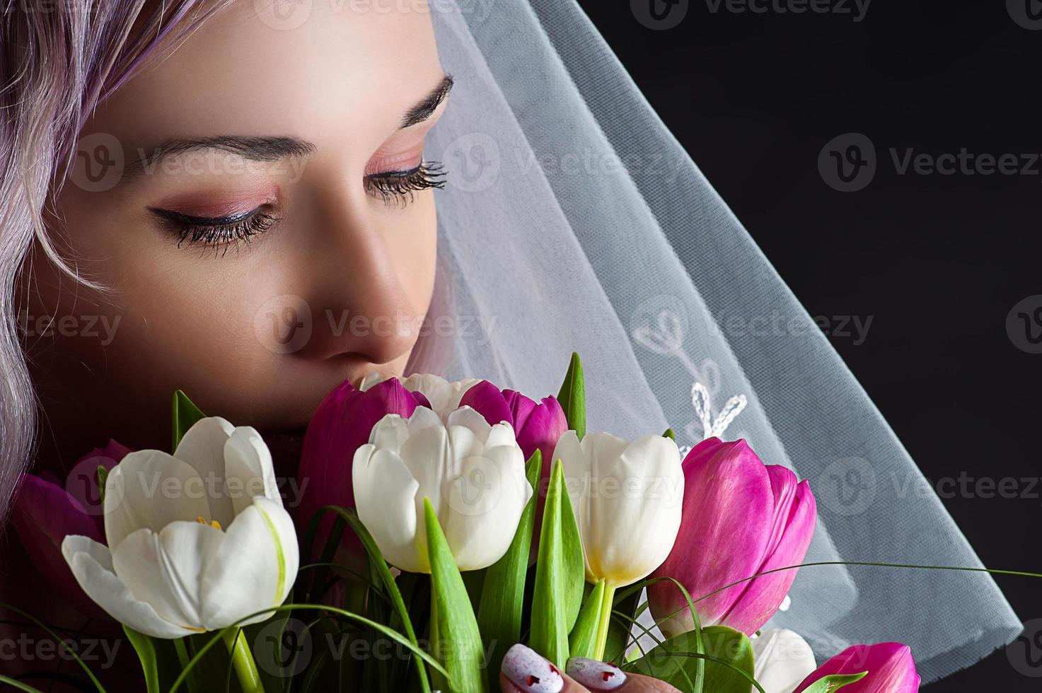 vacker kvinna ansikte med en bukett tulpaner foto