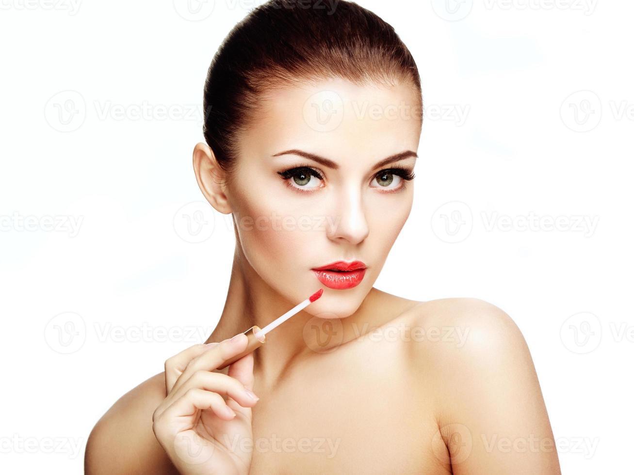 vacker ung kvinna målar läppar med läppstift. perfekt smink foto