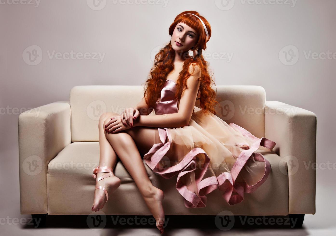 vacker kvinna i lyxig klänning som sitter på soffan. studio skott foto