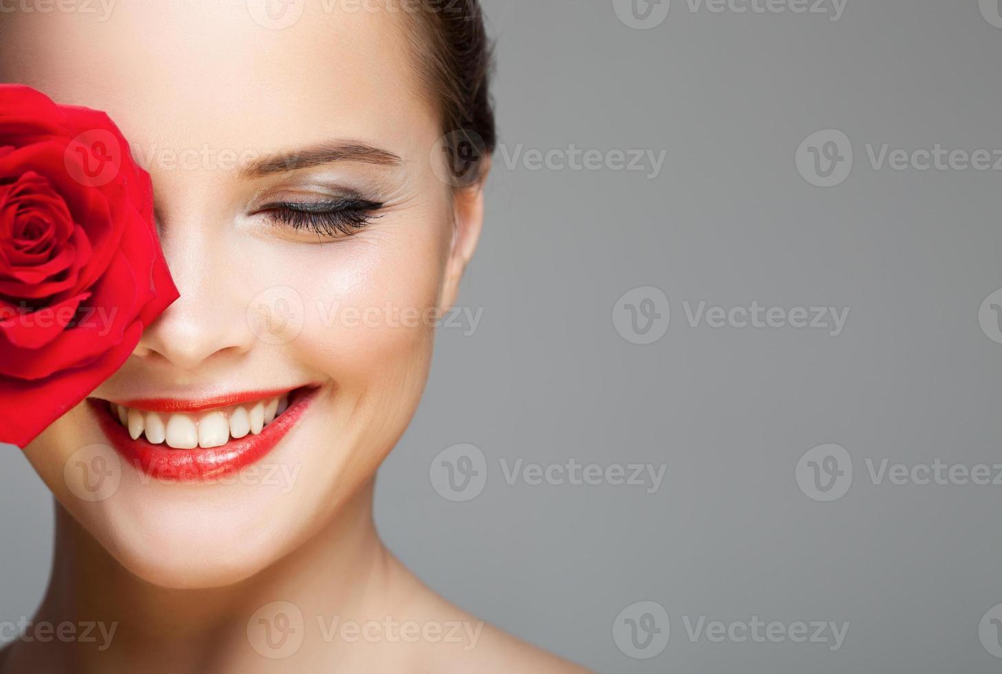 närbild porträtt av vackra leende kvinna med röd ros. foto