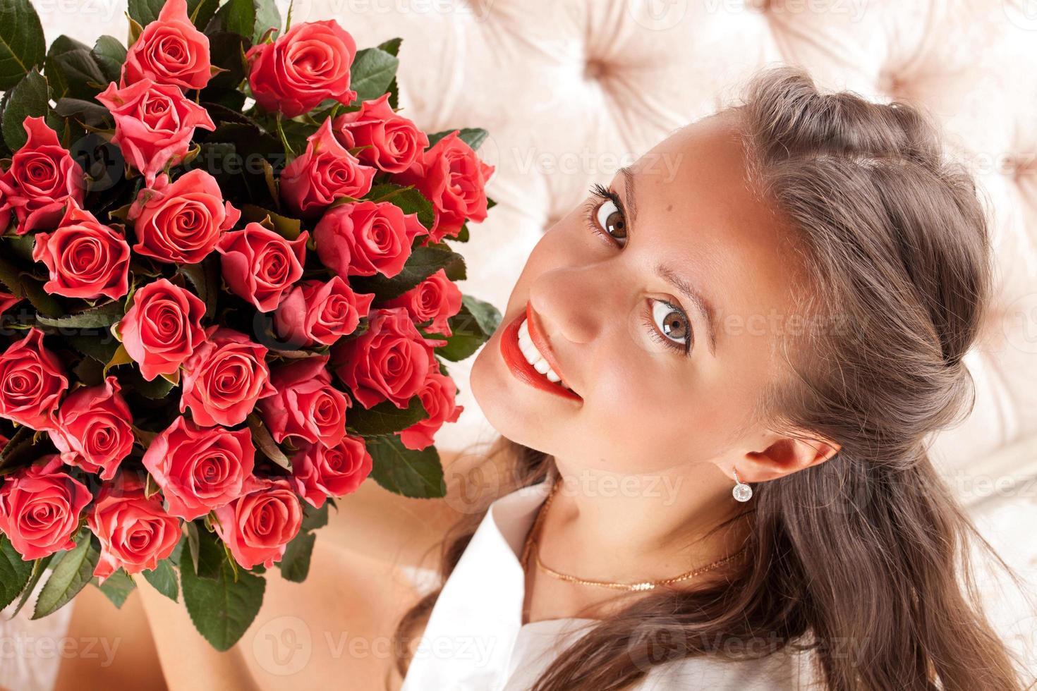 vacker kvinna med en bukett rosor foto