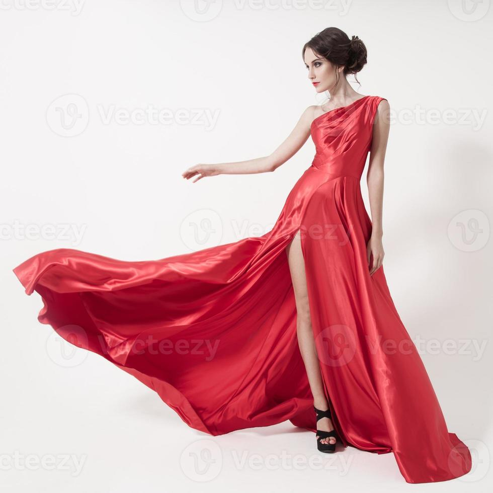 ung skönhetskvinna i fladdrande röd klänning. vit bakgrund. foto
