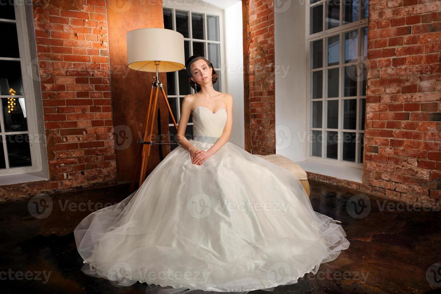 vackert brudsammanträde som poserar i hennes bröllopsklänning. studio. foto