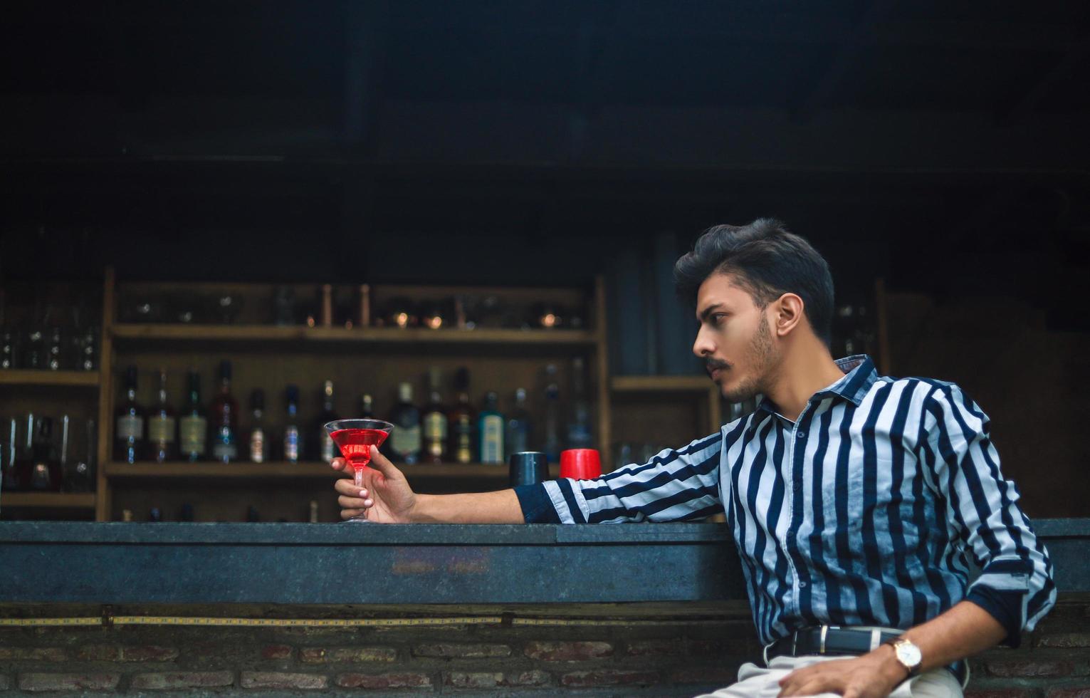 ung man sitter i en bar foto