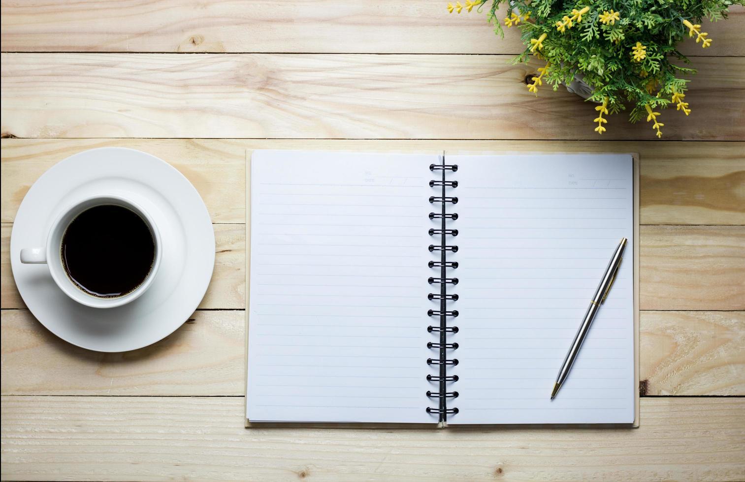 ovanifrån av en anteckningsbok och kaffe foto
