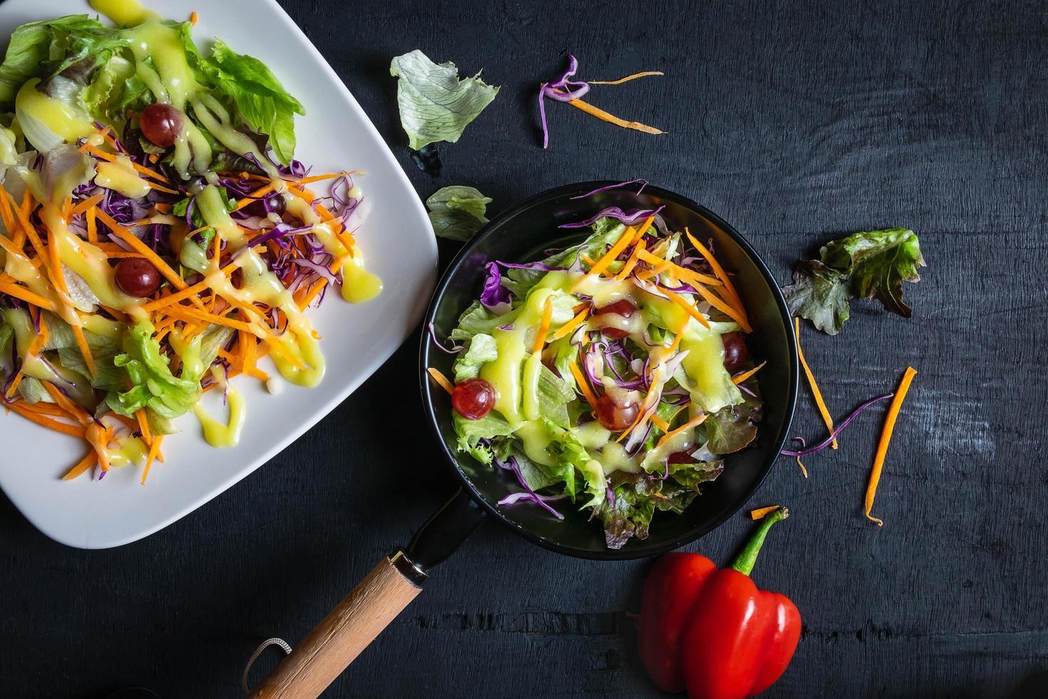 skål med grönsaksallad på det svarta bordet foto