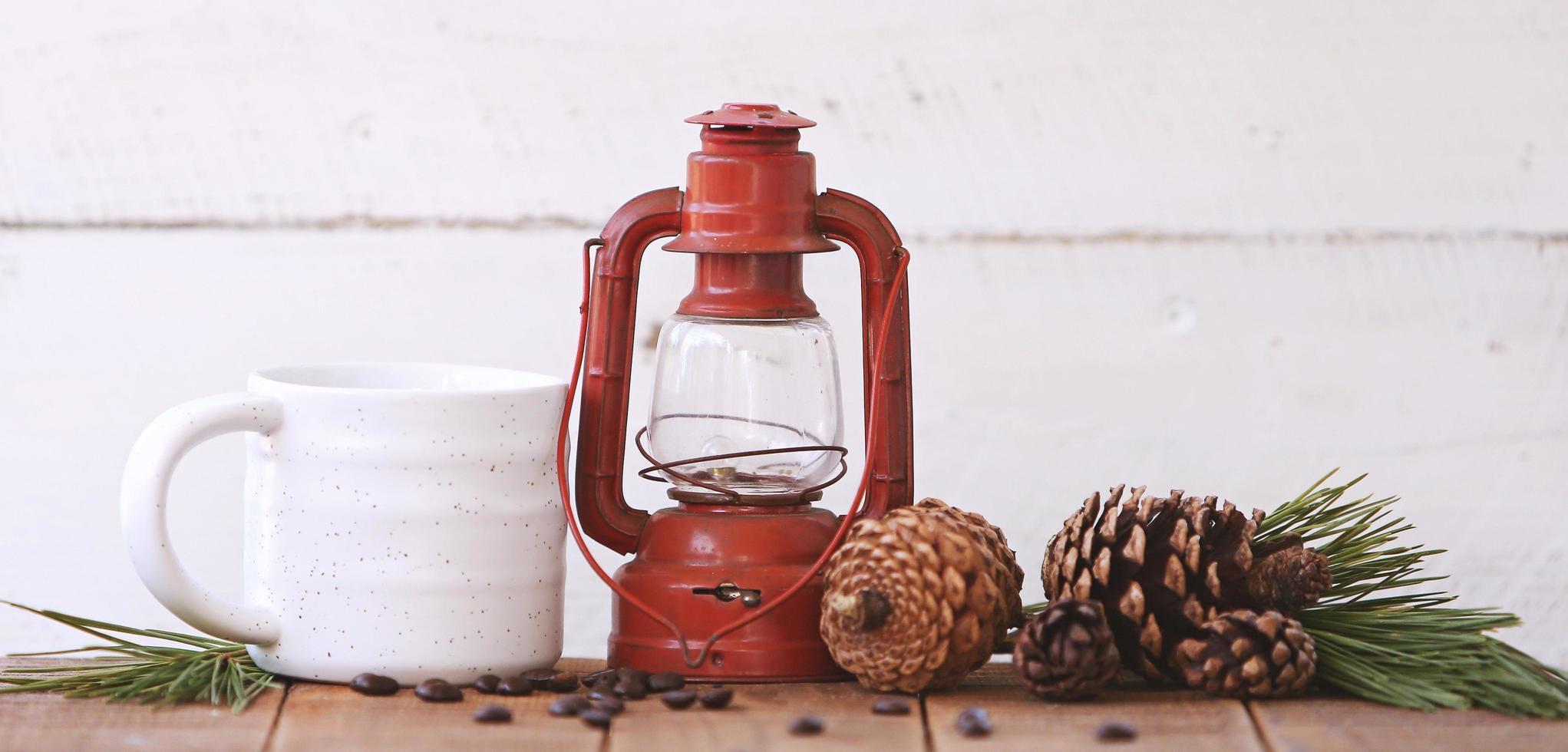 lykta och en kaffekopp med pinecones foto