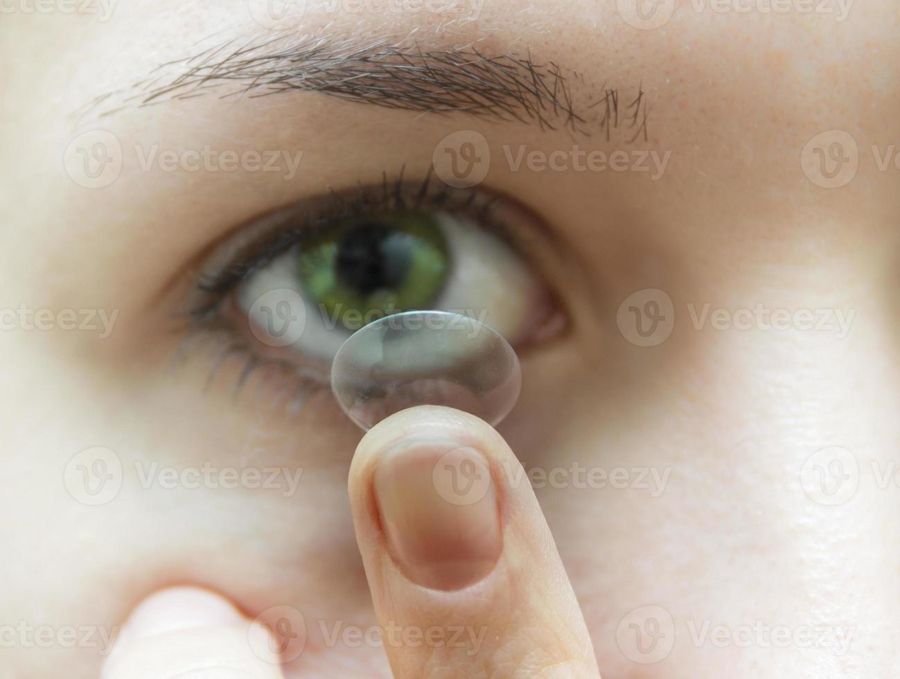 kvinna sätta kontaktlins i ögat foto