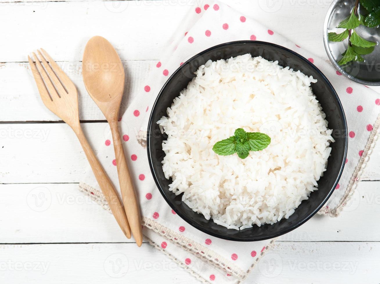 skål full av ris och sked på vit bakgrund foto