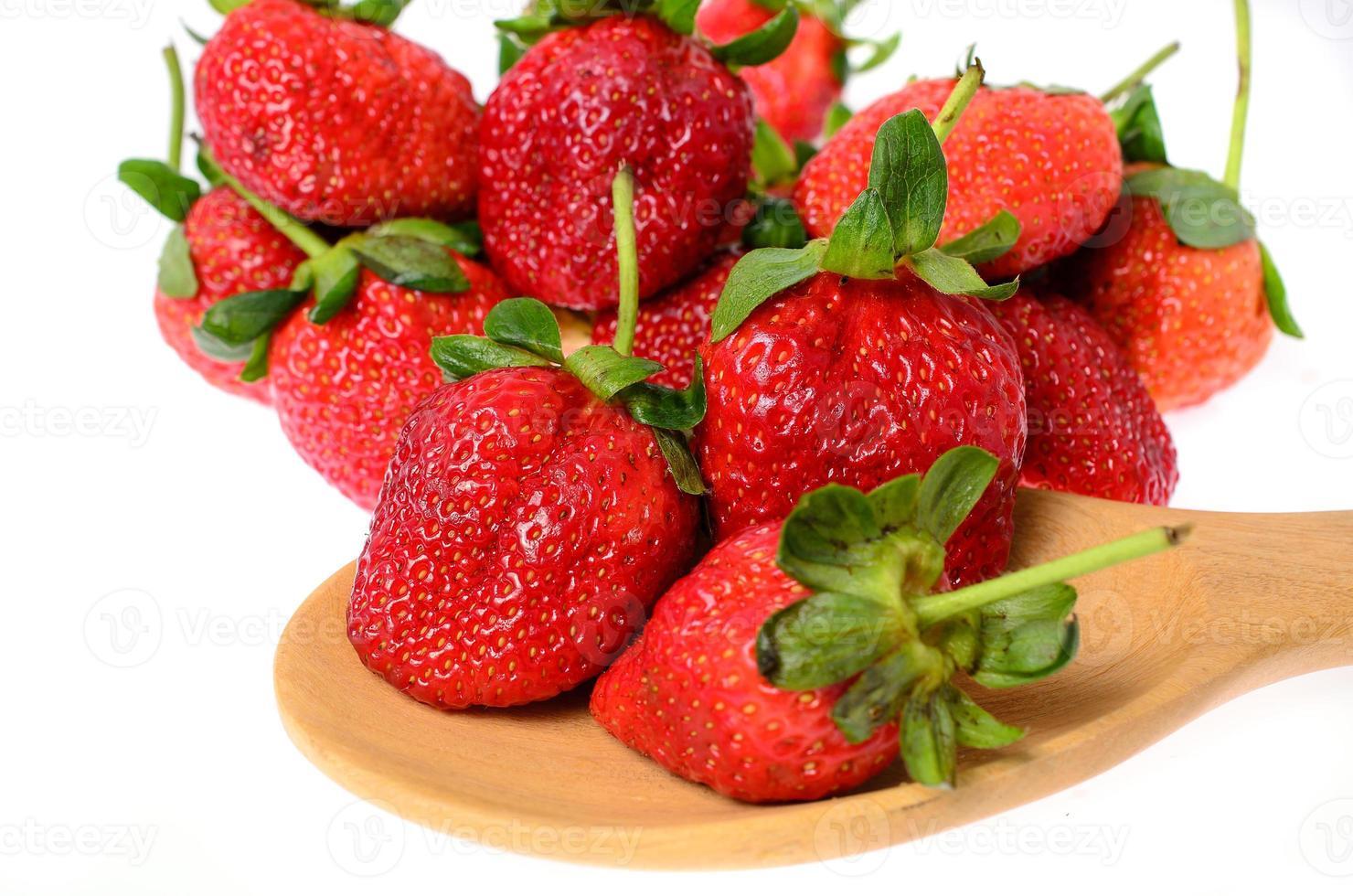 jordgubbar sätta på wodden sked foto