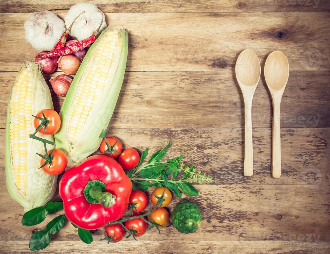 färska ekologiska grönsaker och kryddor på en träbakgrund. foto
