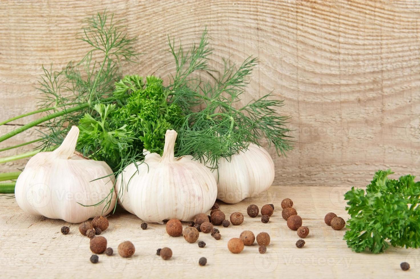 dillblad, vitlök, peppar och kryddpeppar på träplankorbakgrund foto