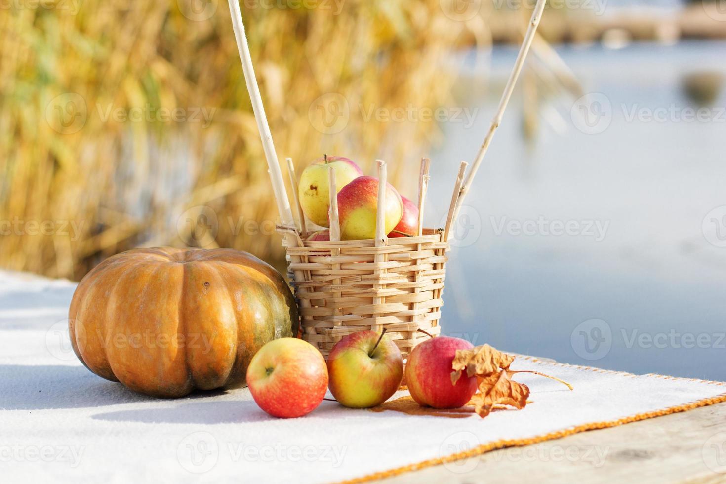 pumpa och korg med äpplen på bordet foto