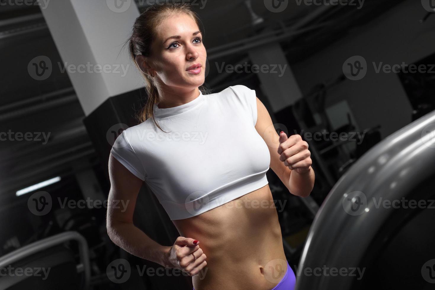 ung kvinna för idrottsman nen kör på ett löpband, i konditionsport foto