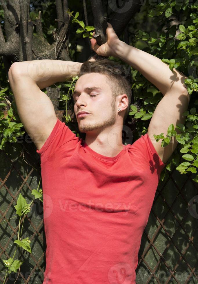 stilig blond ung man som håller trädgren, stängda ögon foto