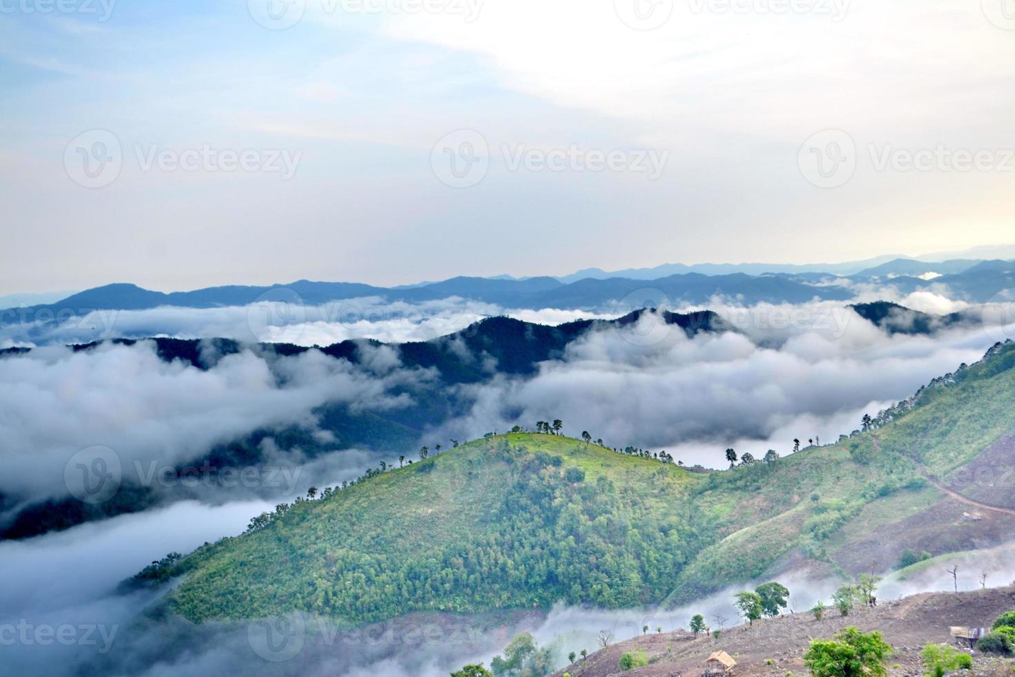 moln rullar över den vulkaniska bergstoppen under en regntid foto