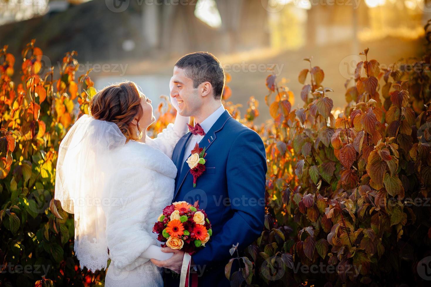 brudgummen och bruden höstbröllop foto