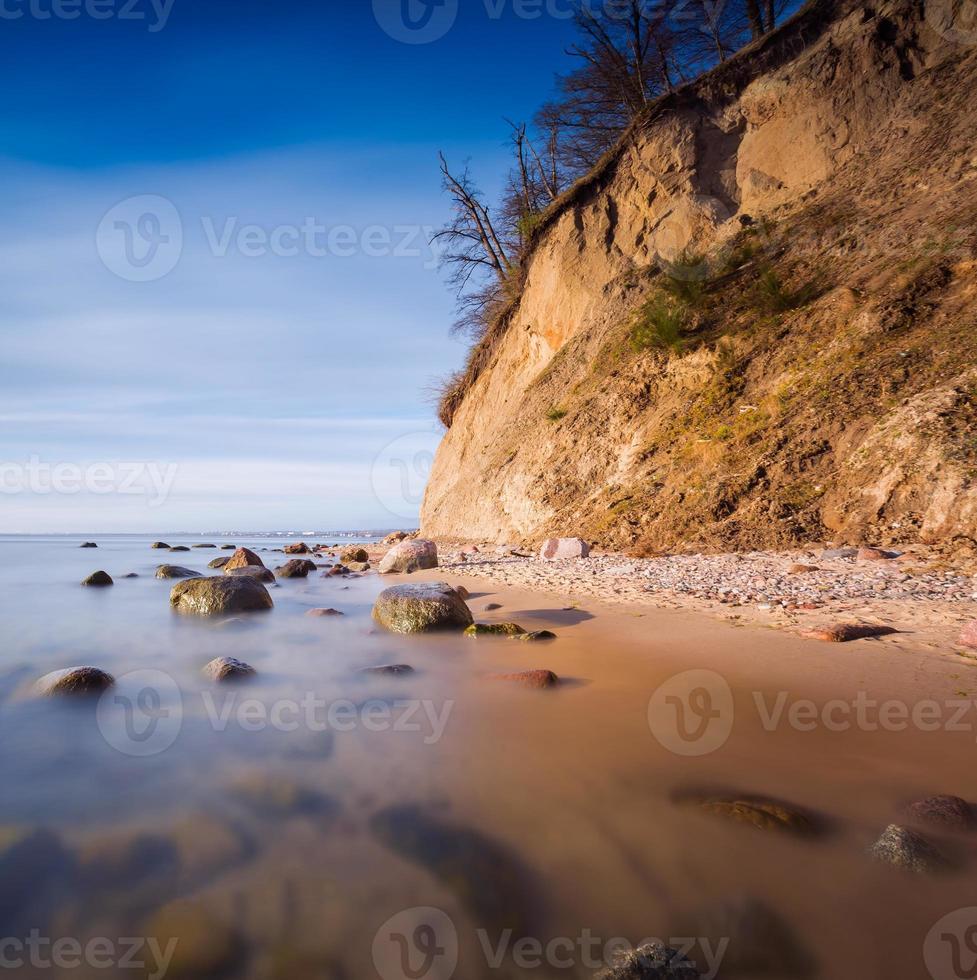 klippa på havsstranden vid soluppgång. baltisk foto för lång exponering