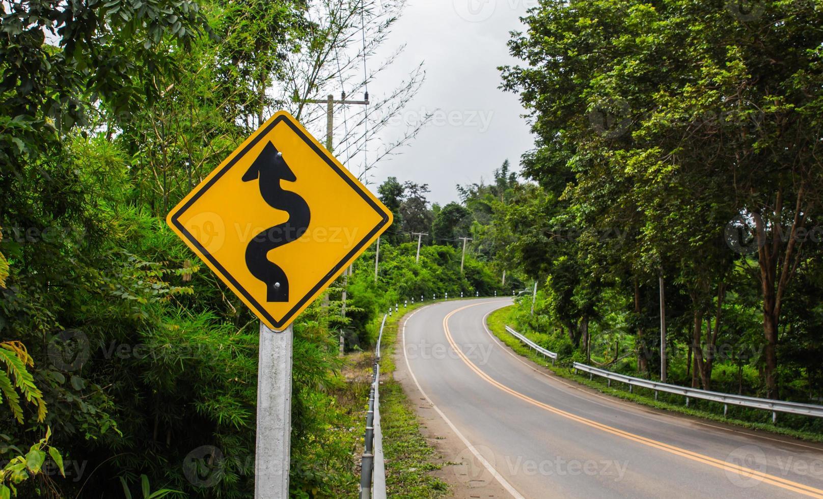 kurvig vägskylt till berget på landsbygden foto