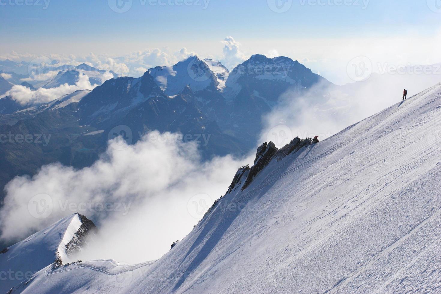 klättrare på en snötäckt bergskam med virvlande moln foto