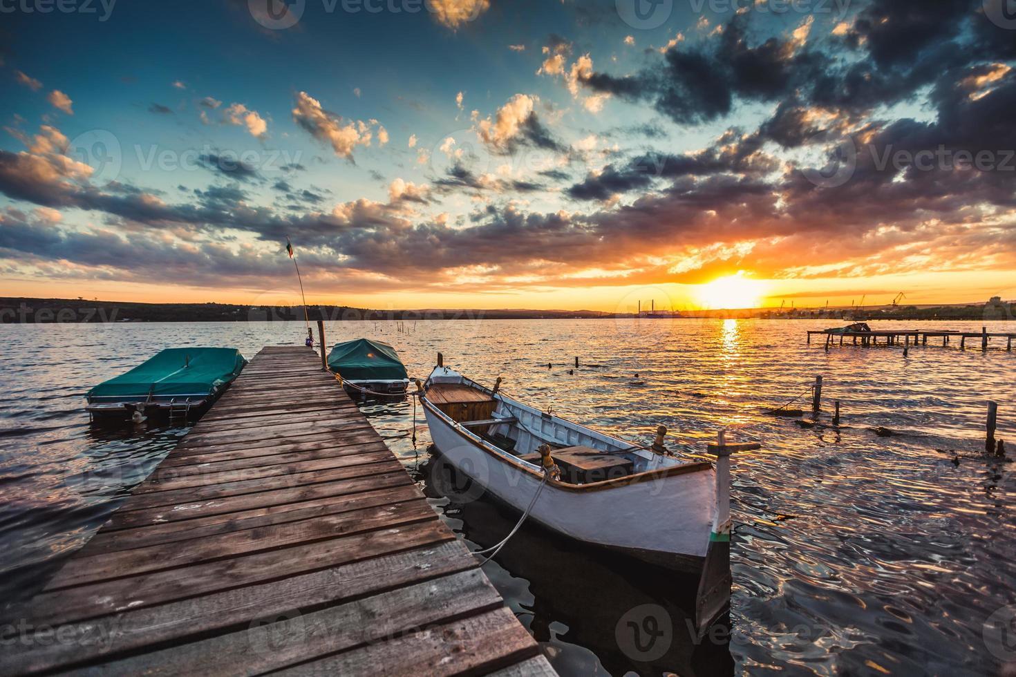 lugn solnedgång med dramatisk himmel och båtar och en brygga foto