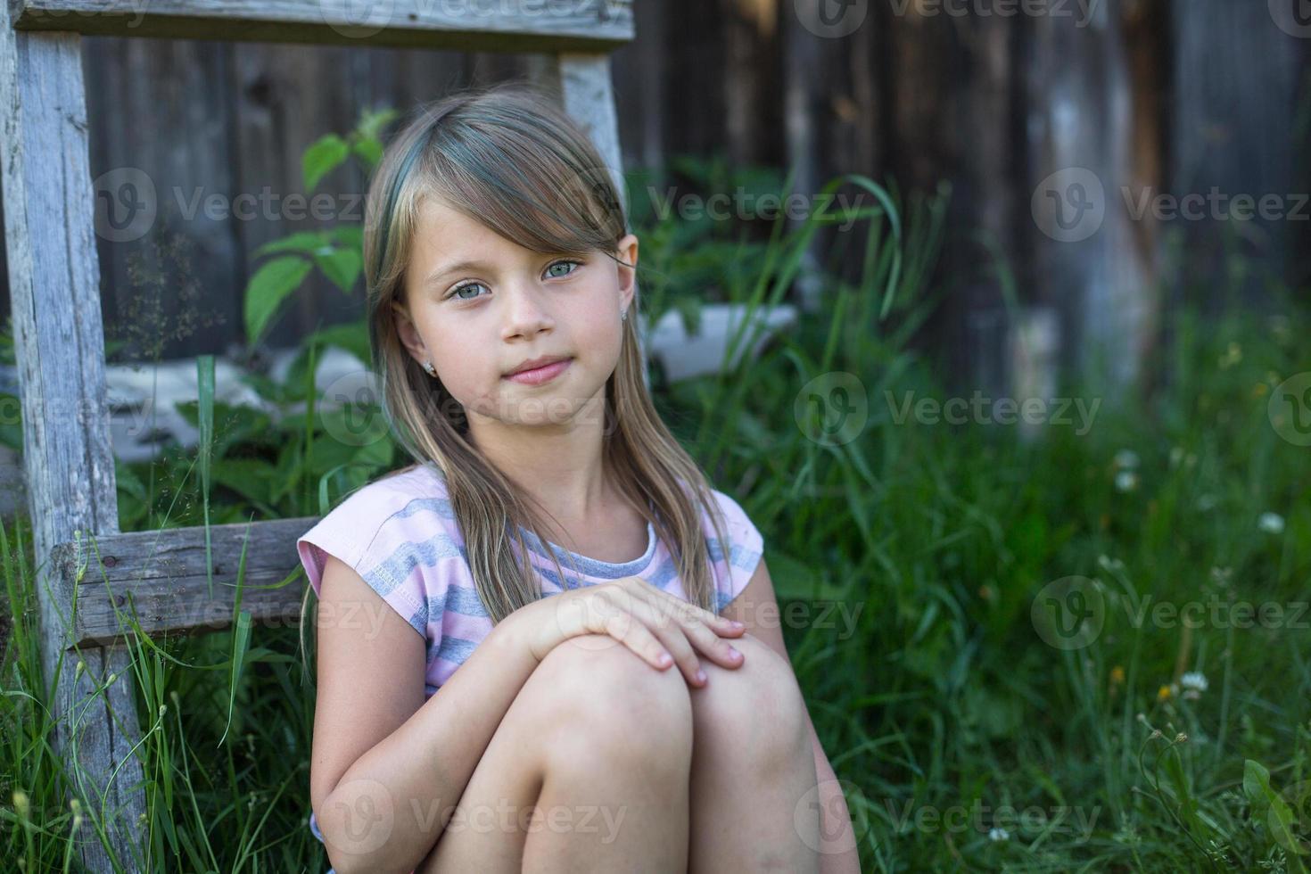 trevlig liten flicka nära ett lantligt hus. foto