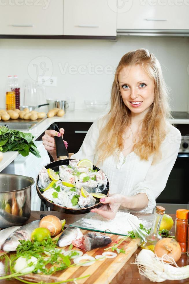 kvinna som lagar fisk i stekpanna foto