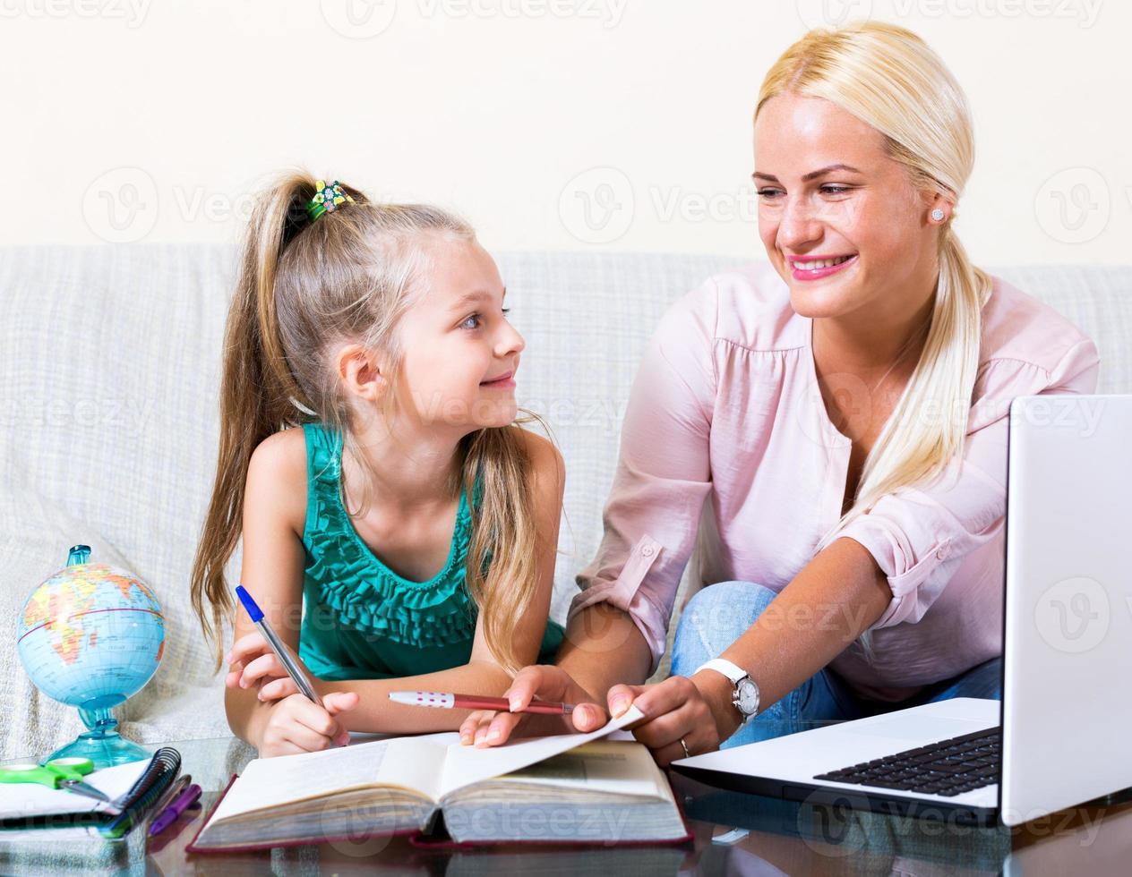 glad mamma som hjälper den lilla dottern foto