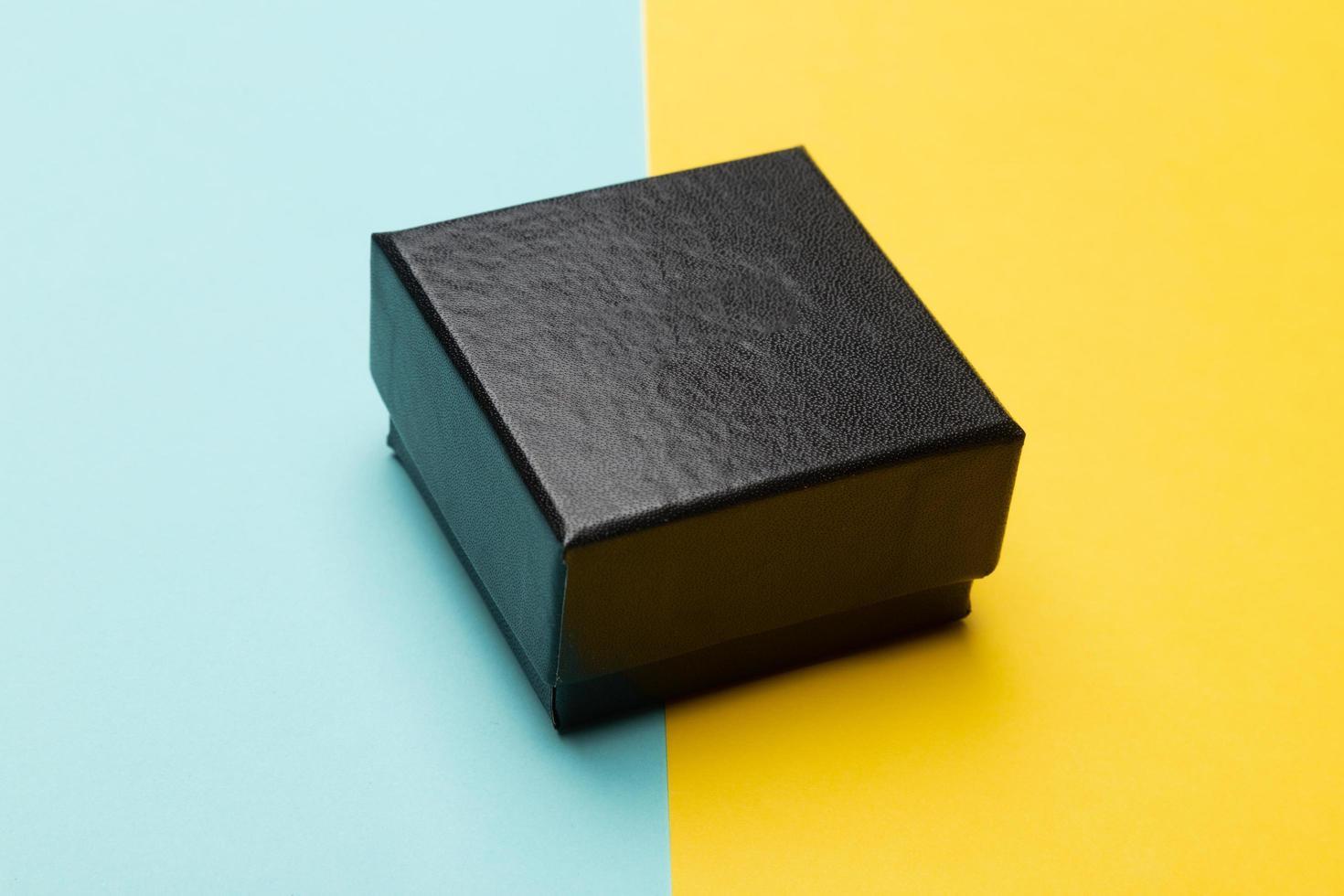 mini svart låda isolerad på halv gul halvblå bakgrund foto