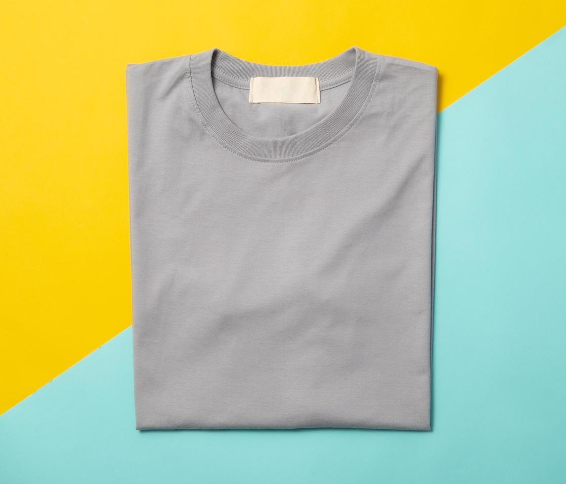 grå vikta t-shirt isolerad på gul och blå bakgrund foto