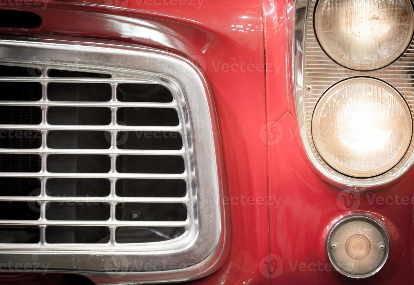 närbild av galler och strålkastare av rött fordon foto