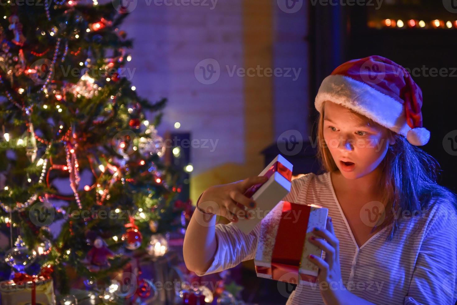 jultid, en uttrycksfull ung flicka som öppnar sin presentförpackning foto