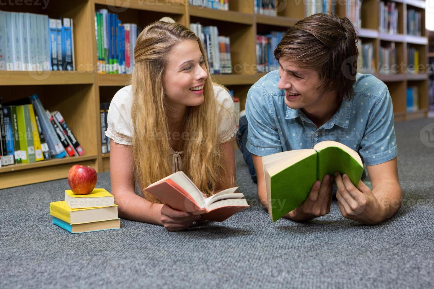 studenter som läser bok som ligger på biblioteksgolvet foto