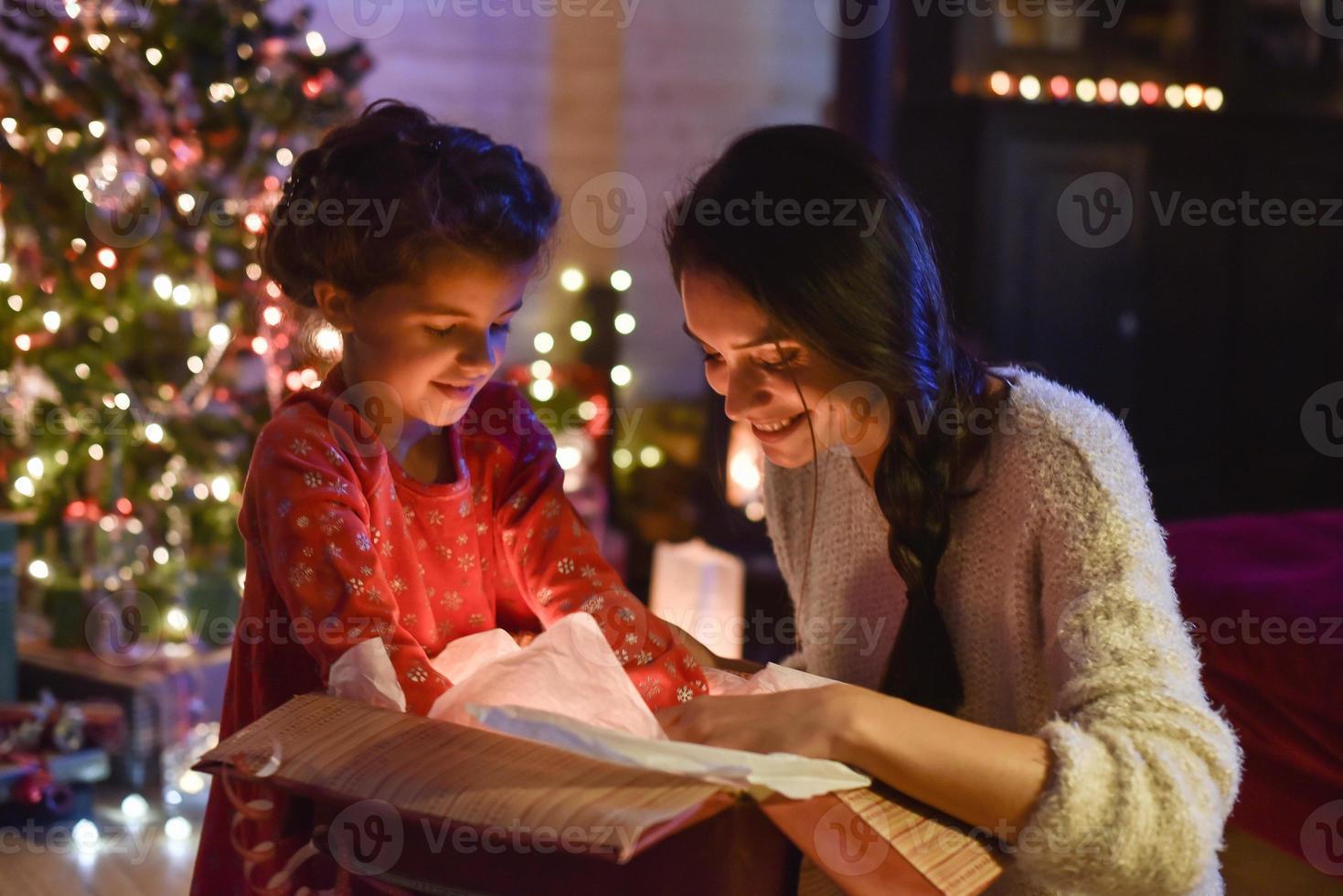 jul, mamma och hennes dotter öppnar en gåva nära trädet foto