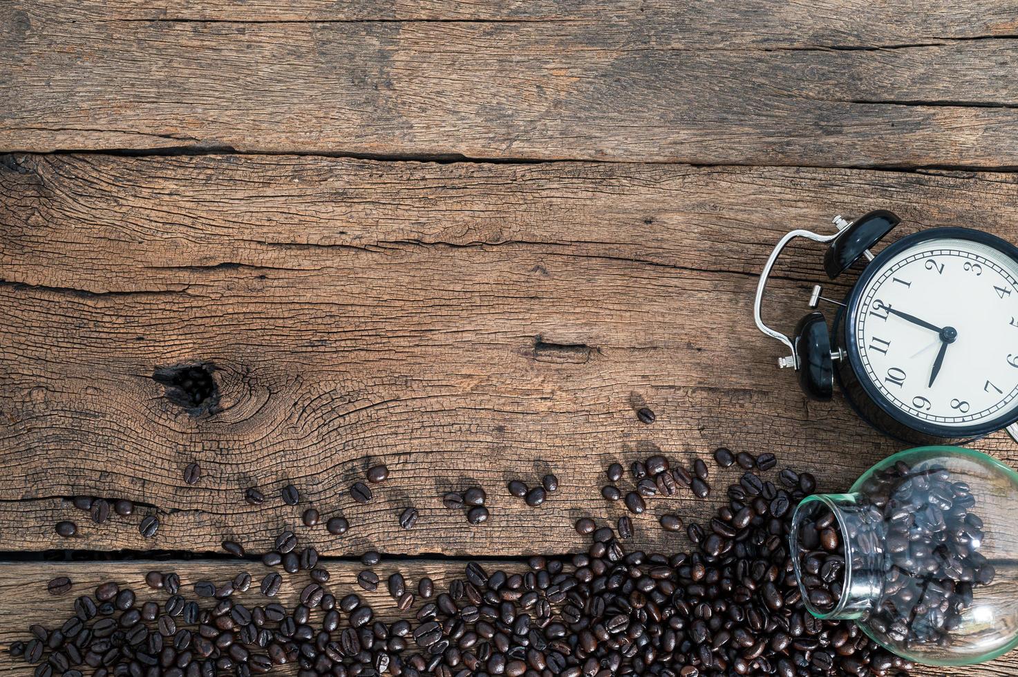 klocka och kaffebönor på skrivbordet foto