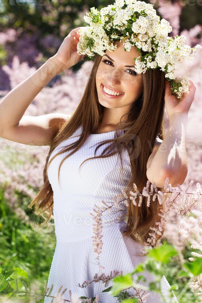 vacker flicka på naturen i krans av blommor foto