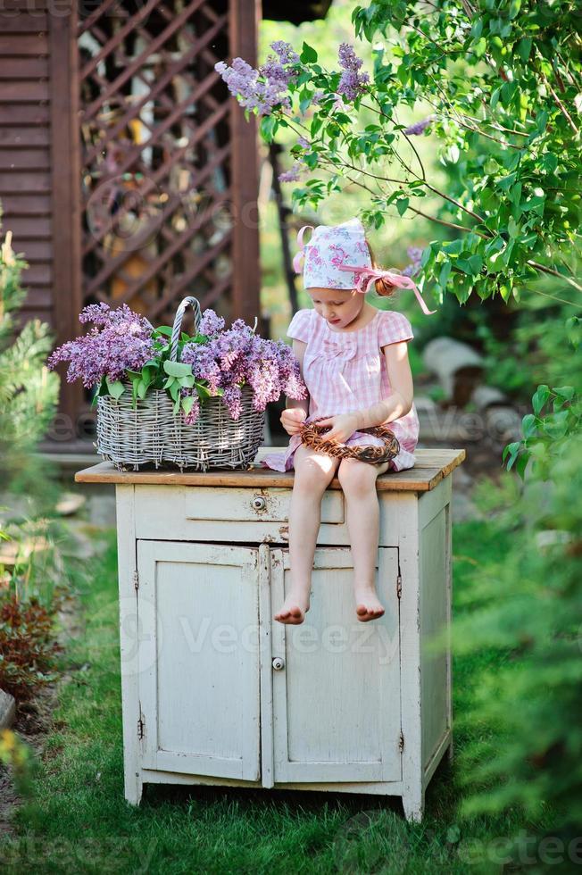söt barnflicka som gör lila krans i vårblommande trädgård foto