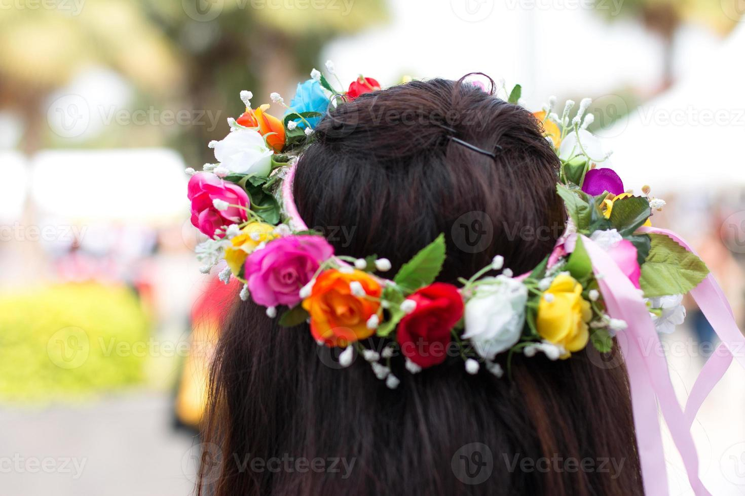 flicka med färgglad blommakrans foto