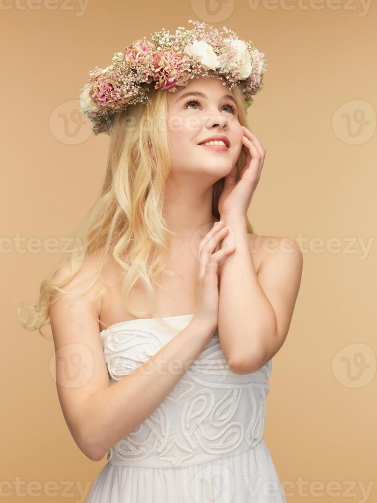kvinna i vit klänning som bär krans av blommor foto