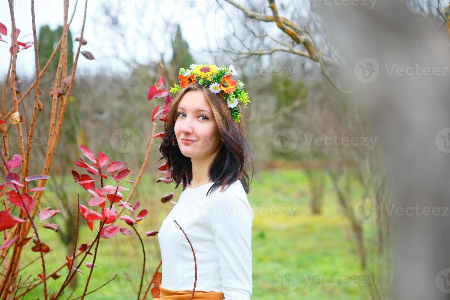 ung brunettflicka med blommakrans i höstparken foto