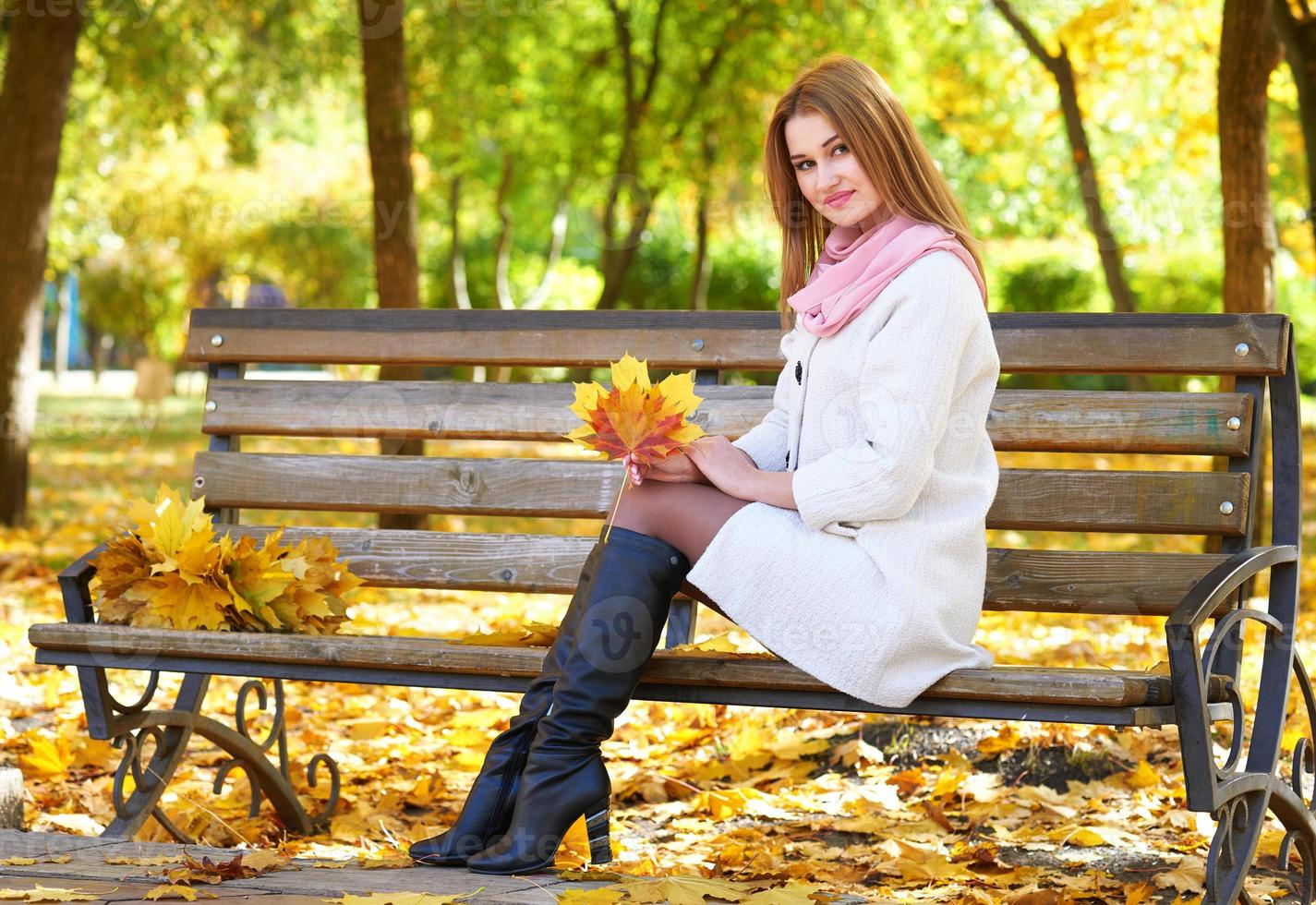 flickastående med löv i höststadsparken foto