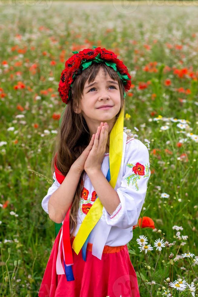 liten ukrainsk tjej ber för fred foto