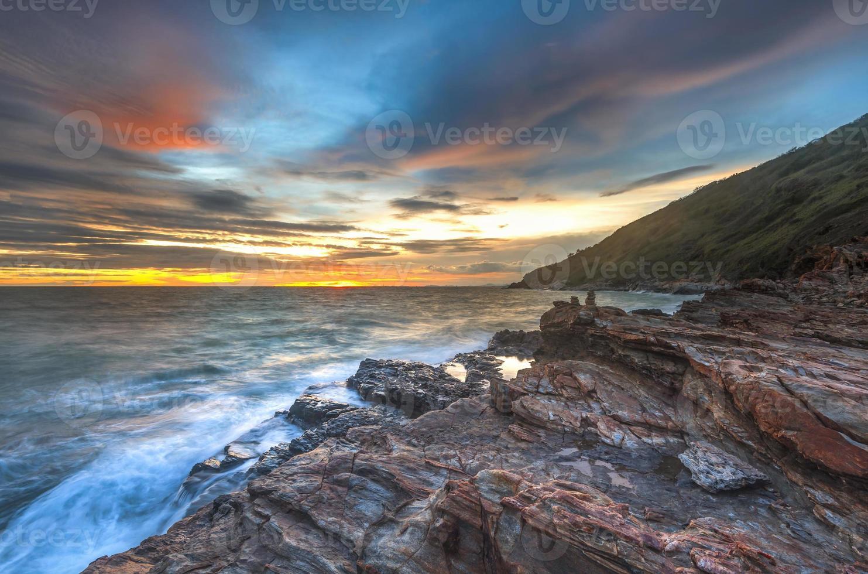 solnedgång vågor lash line inverkan rock på stranden foto